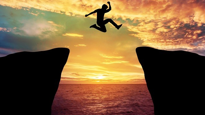 Man jump through the gap between hill.
